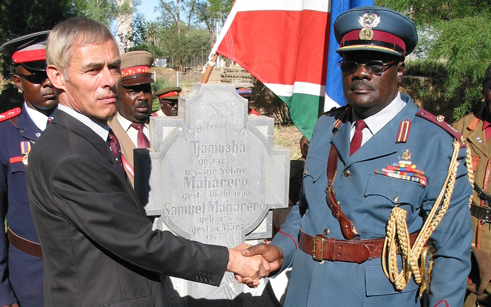 Handshake at the grave of Samuel Maharero in January 2004 in Okahandja at the 100-year memorial of the beginning of the Herero uprising: the then-embassador of Germany, Wolfgang Massing, and the late Herero Paramount Chief, Kuaima Riruako